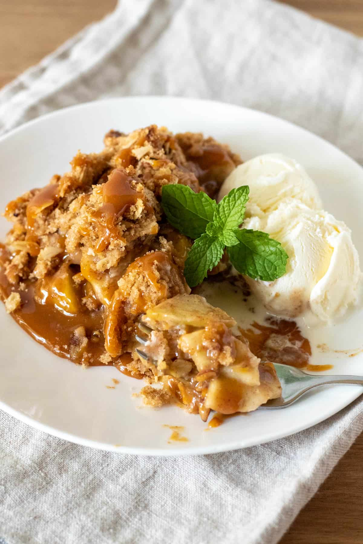 Piece of Dutch apple pie with caramel sauce and vanilla ice cream on white plate.