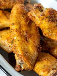 Air fryer chicken wings piled in a pan.